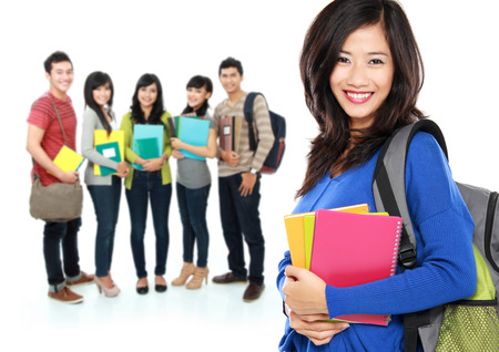 Female happy student carrying bag and books with a group of people at the background Stock Photo - 26771563