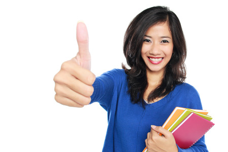 portrait of Young female student with books showing thumb up isolated over white background