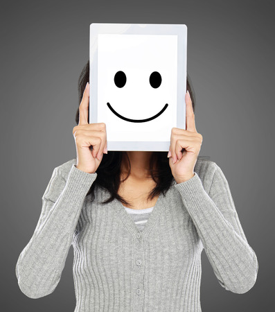woman cover her face with tablet showing happy expression icon