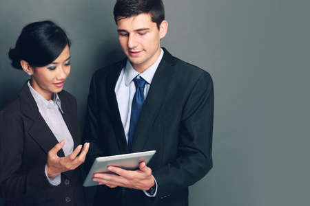 Image of two young business people at the meeting using tablet pc photo