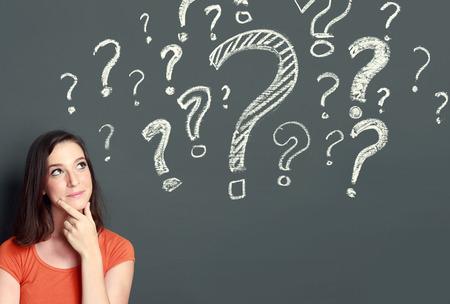 question mark: giovane ragazza con il punto interrogativo su uno sfondo grigio