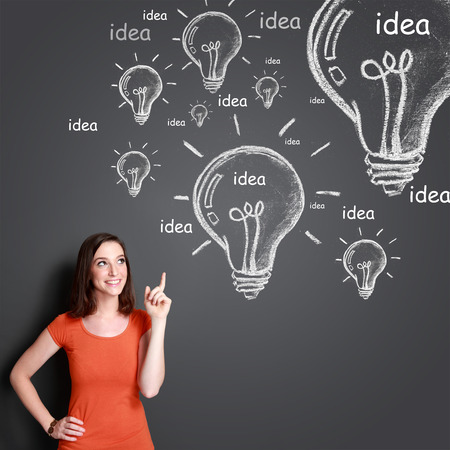 portrait of attractive young woman with lightbulb icon on top of her. idea concept photo