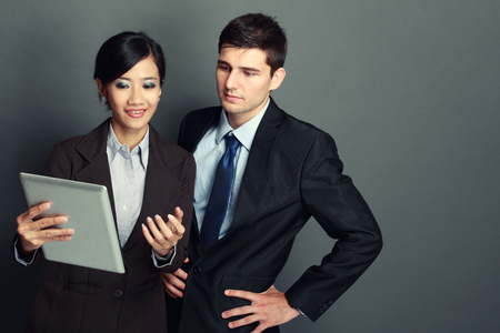 strategy meeting: Image of two young business people at the meeting using tablet pc