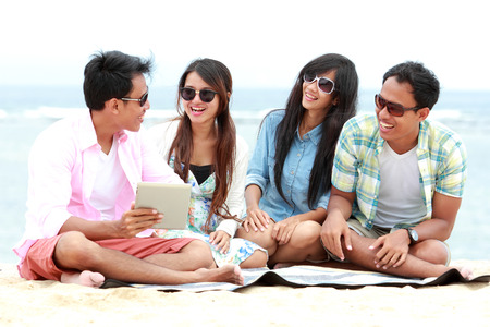 portrait of Group Friends Enjoying Beach Holiday together with tablet pc. technology and internet concept photo