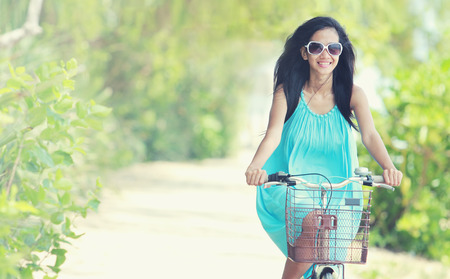carefree: carefree woman having fun and smiling riding bicycle at the beach Stock Photo