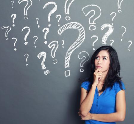 mujer joven con signo de interrogación sobre un fondo gris