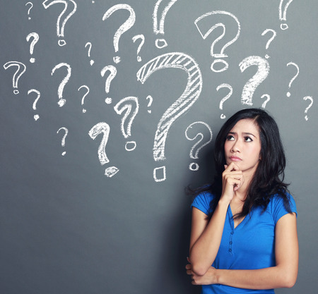 young woman with question mark on a gray background Stock Photo