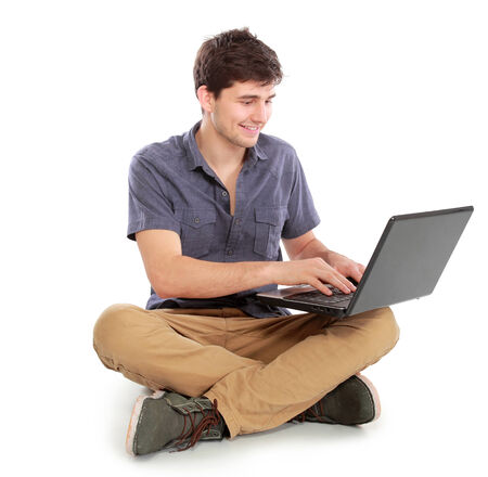 portrait of happy young man sitting while using laptop computer on white background photo