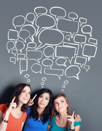 portrait of multi racial three girl best friend looking up to bubble speech. social media concept