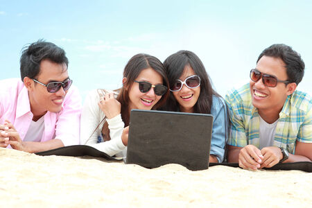 portrait of Group Friends Enjoying Beach Holiday together with laptop pc. technology and internet concept photo