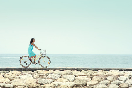 happy healthy woman: carefree woman having fun and smiling riding bicycle at the beach Stock Photo