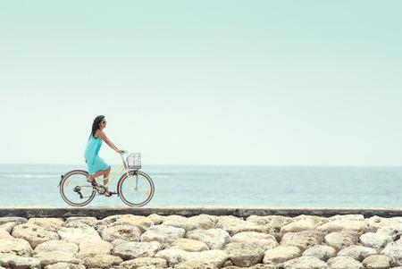 mujer alegre: mujer despreocupada divertirse y sonriente en bicicleta a caballo en la playa