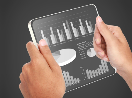 image of hands holding futuristic transparent tablet pc. business chart financial concept photo