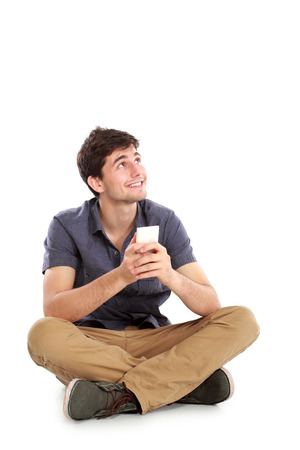 young male smiling using mobile phone thinking and looking up against white background photo