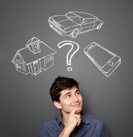 financial questions: Mortgage and credit concept. Young man planning his future Stock Photo