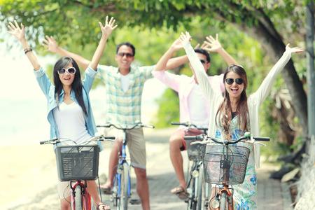 andando en bicicleta: amigos despreocupados grupo divertirse y sonriente que monta la bicicleta durante el día de verano Foto de archivo