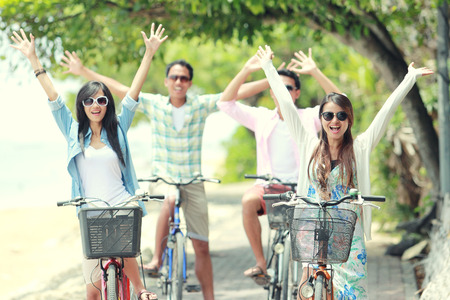 carefree group friends having fun and smiling riding bicycle during the summer day Stock Photo