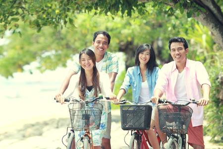 屈託のないグループの友達と楽しい夏の日に乗って自転車を笑顔 写真素材