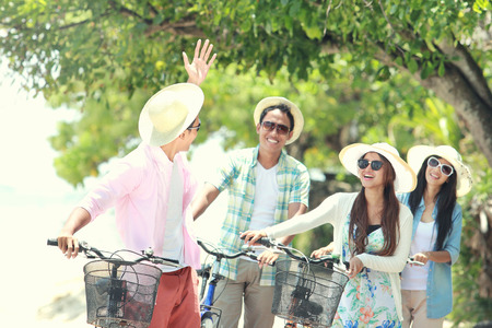 carefree group friends having fun and smiling riding bicycle during the summer day photo