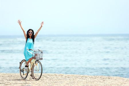 屈託のない女と楽しんで、ビーチでの乗馬の自転車の笑みを浮かべて 写真素材