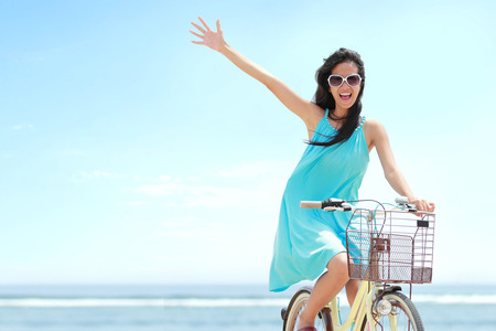 andando en bicicleta: mujer despreocupada divertirse y sonriente en bicicleta a caballo en la playa