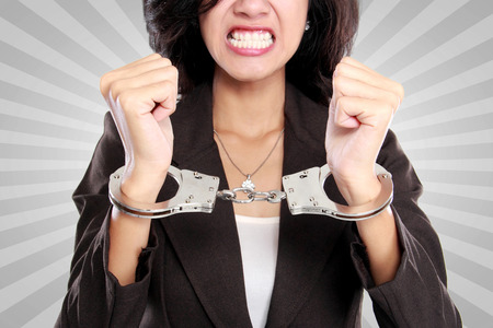 arrest women: portrait of young business woman in handcuffs