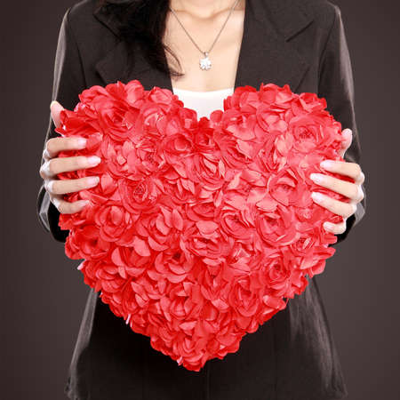 congenial: portrait of Business woman hand with red heart over red background