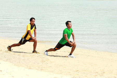 portrait of two man exercise on the beach photo