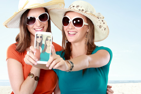 attractive girlfriends in the summer day doing self portrait using mobile phone photo