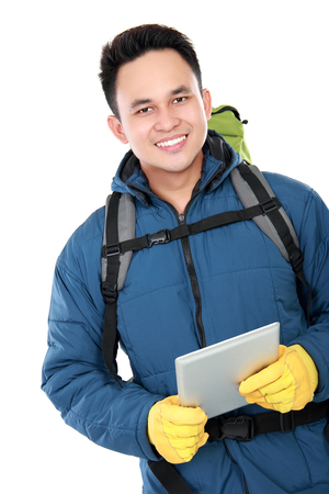 portrait of a smiling male hiker with backpack using tablet computer isolated on white background photo