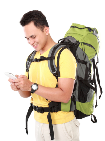 internet explorer: portrait of a smiling male hiker with backpack using mobile phone isolated on white background Stock Photo