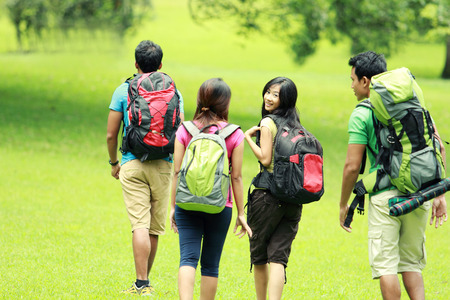 backpackers: group of people hiking together. walking on the grass