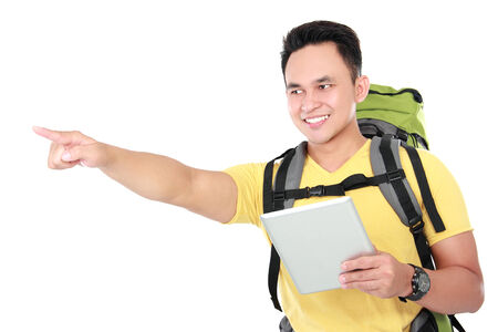 portrait of a smiling male hiker pointing to the direction while using tablet computer photo