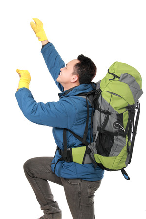 portrait of male hiker with backpack climbing isolated on white background photo