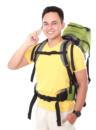 Portrait of young man tourist with backpack using mobile phone isolated on white background photo