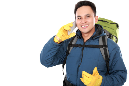 portrait of a smiling male hiker with backpack using mobile phone isolated on white background photo