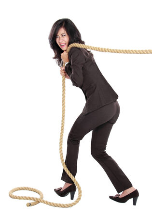 Business competition. Young business woman pulling a rope isolated on white background
