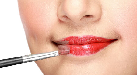 close up of woman applying lipstick on her lips isolated on white background photo