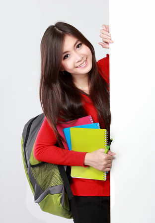 Portrait of Pretty asian female student portrait with blank white board isolated over white background photo