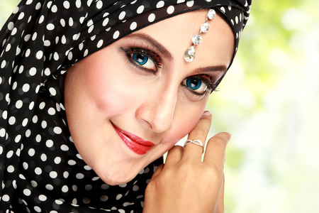 Fashion portrait of young beautiful muslim woman with black scarf photo