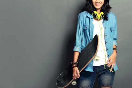 portrait of Beautiful young woman with skateboard photo