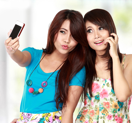 Two young female friends taking a picture of themselves on a smart phone. selfie