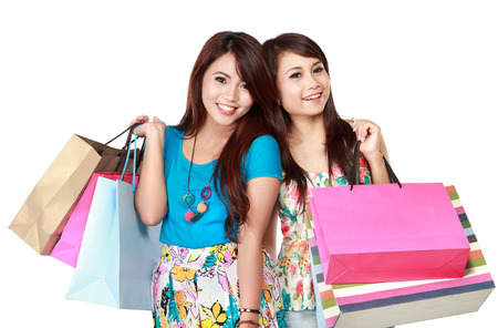 Portrait of two young woman happy holding shopping bags, isolated over white background photo