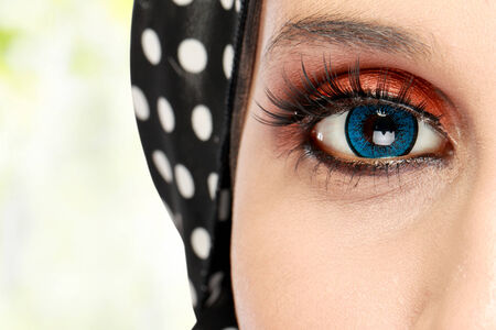 Closeup of beautiful woman eye with makeup. woman with scarf photo