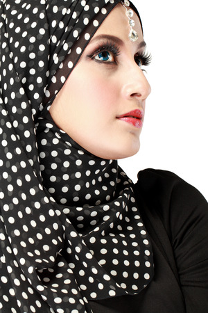 Fashion portrait of young beautiful muslim woman with black scarf isolated on white background photo