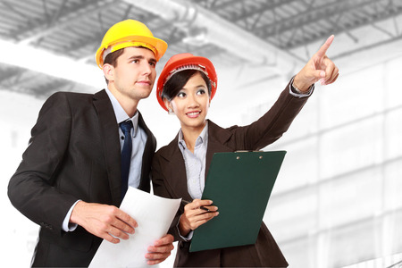 asian architect: A team of male and female architect pointing at construction site Stock Photo