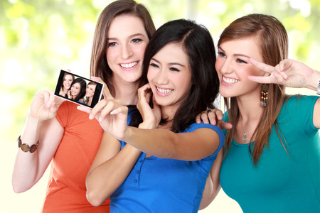 multi race: Three multi racial young girl friends taking a picture of themselves on a smart phone. selfie