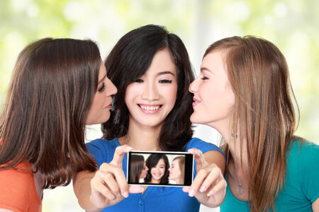 Three multi racial young female friends taking a picture of themselves on a smart phone. selfie photo