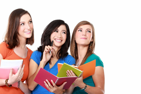studygroup: Portrait of a three young students holding a book isolated on white background