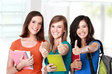 studygroup: Portrait of a three young female student together showing thumbs up